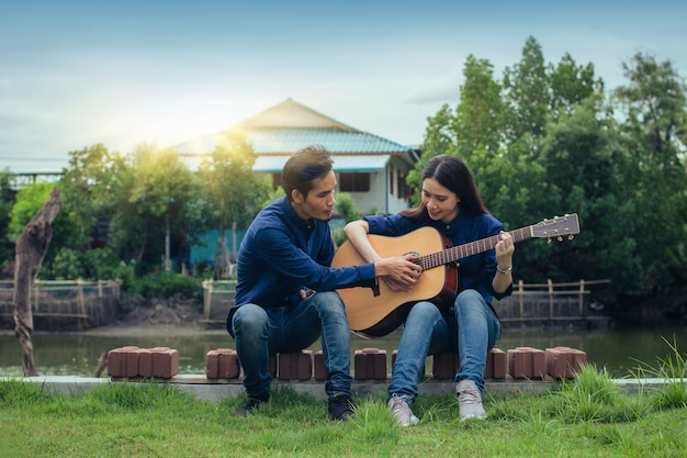 Man training guitar with woman sitting in park nature rest summer holiday