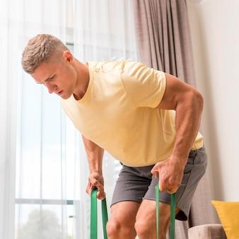 Man training at home using elastic band