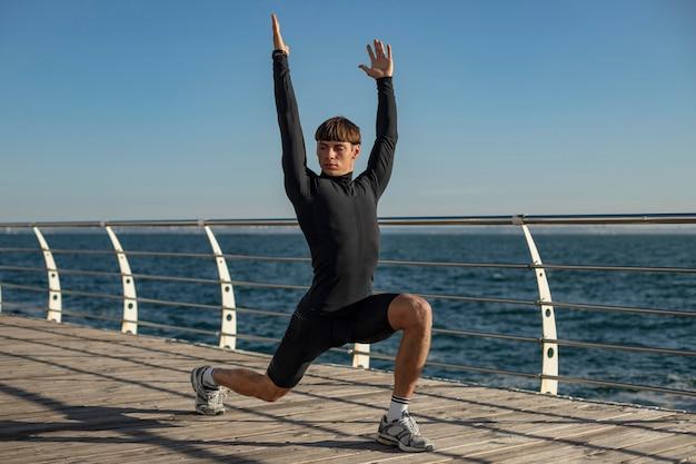 해변에서 activewear 훈련하는 남자