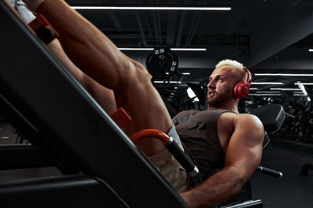 シミュレーターで脚をトレーニングする男性。ヘッドホンで音楽にジムで彼の足で運動をしている若い男。