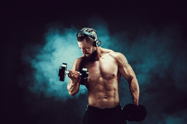 Man training muscles with dumbbells in studio on dark background with smoke.