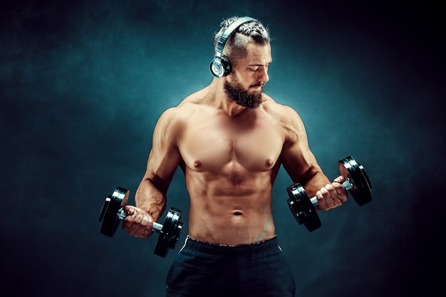 Man training muscles with dumbbells in studio on dark background.