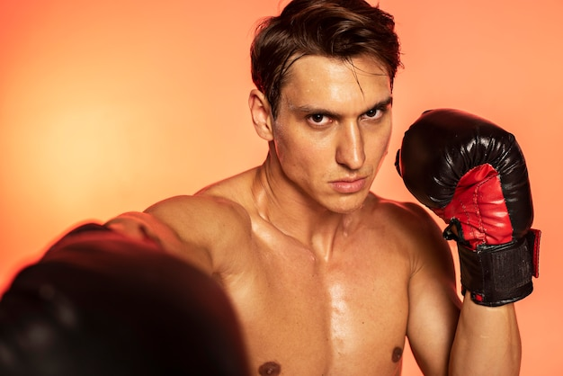 Man training with boxing gloves close up