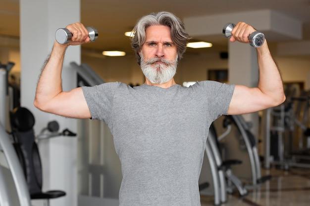Тренировка человека с гантелями в спортзале