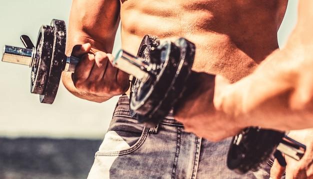 ダンベルでトレーニングする男性。ダンベル。筋肉のボディービルダーの人、ダンベルでエクササイズ。強力なボディービルダー。ダンベルのある筋肉