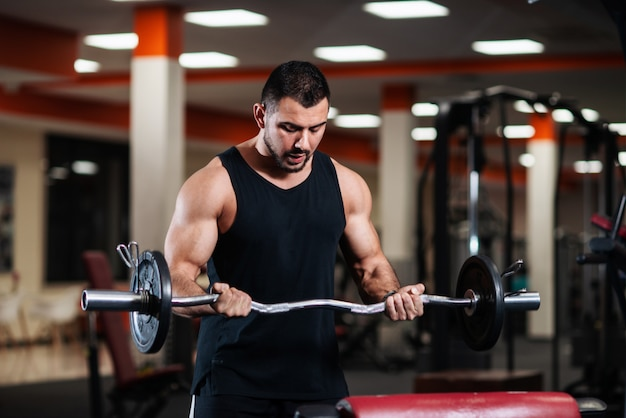 Man trains biceps in the gym. muscular bodybuilder guy doing exercises with a barbell.