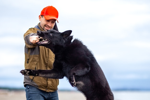 男は黒海沿岸、ポティの砂浜でジャーマンシェパードを訓練します