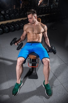Man trains in the gym, fitness and abdominal press