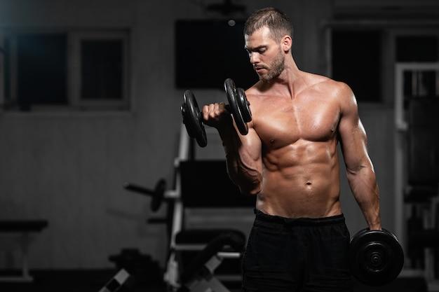 男はジムで訓練します。アスレチック男は彼の二頭筋をポンピング、ダンベルで訓練