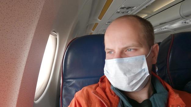 男性は、保護用医療マスクを着用して飛行機で白人を旅行します。保護呼吸器を備えた航空機での男性観光客。コンセプトウイルス保護コロナウイルスパンデミックsars-cov-2covid-192019-ncov。
