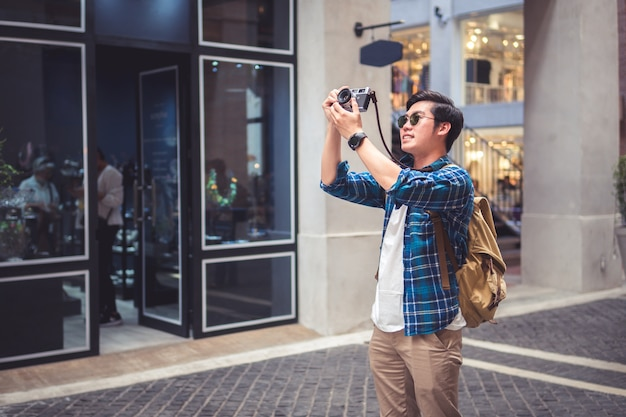 Man travel concept tourist taking photo by phone and put up hand overhead to shoot street and city