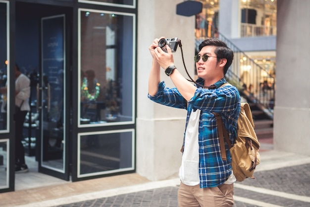 Man travel concept tourist taking photo by phone and put up hand overhead to shoot walking street