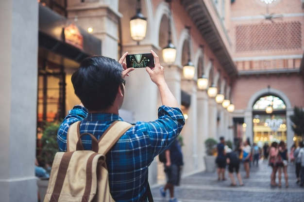 Man travel concept tourist taking photo by phone and put up hand overhead