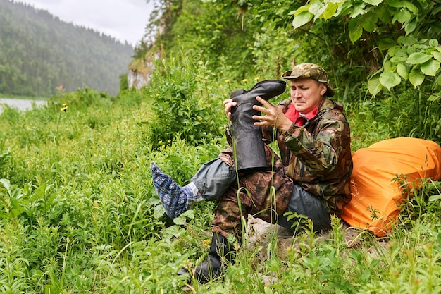 Man traveler dressed in military style, changing boots using a footwraps instead of a sock