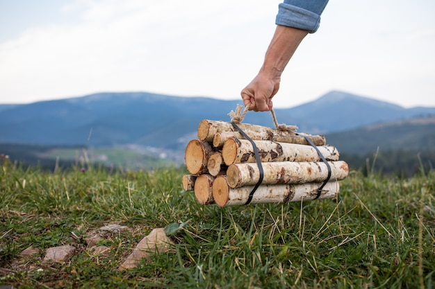 Man traveler hands holding firewood for fire in mountains. place for inscription.