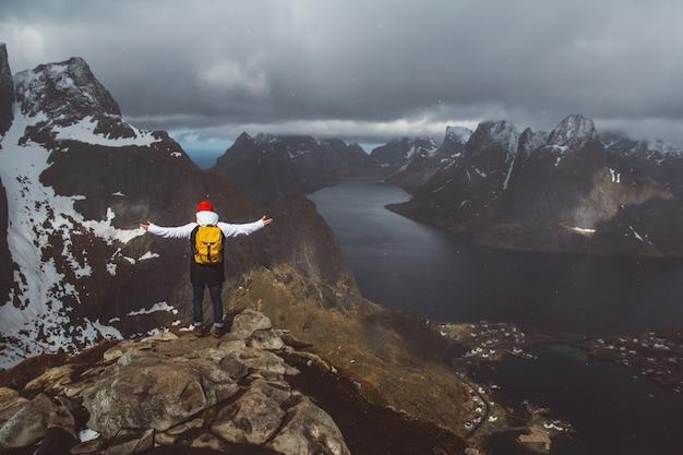 Man traveler hiking on reinebringen mountain ridge in norway lifestyle adventure traveling.