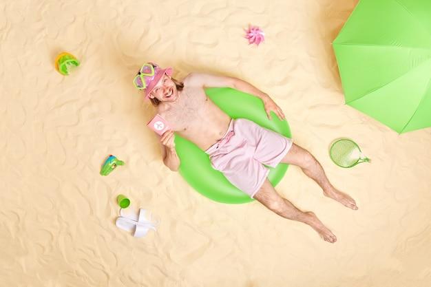 Человек-путешественник с паспортом лежит в позах для плавания на песчаном пляже в окружении разных предметов, отдыхает у моря, имеет счастливое настроение