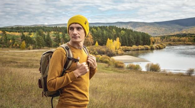 노란색 모자를 쓰고 배낭을 메고 스웨터를 입은 남자 여행자가 강, 가을 황금빛 숲, 언덕 앞에 서 있습니다. 자유, 여행, 하이킹의 개념