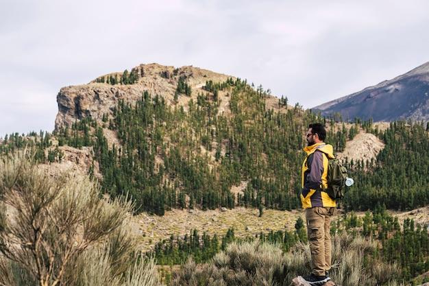トラベルライフスタイルの周りの澄んだ空と山頂の男の旅行者