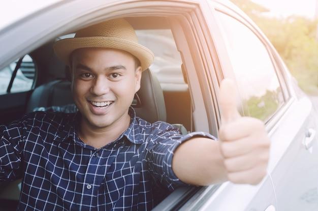 Путешественник человек на дороге. внутри автомобиля показывает палец вверх на открытом воздухе. готов уходить.