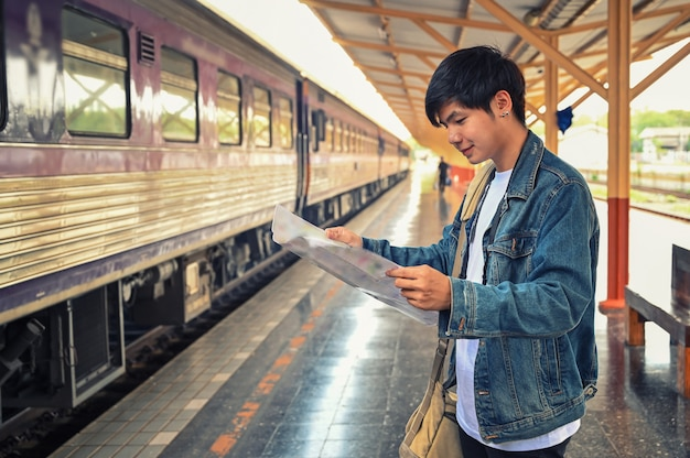 Man traveler reading a map on train station