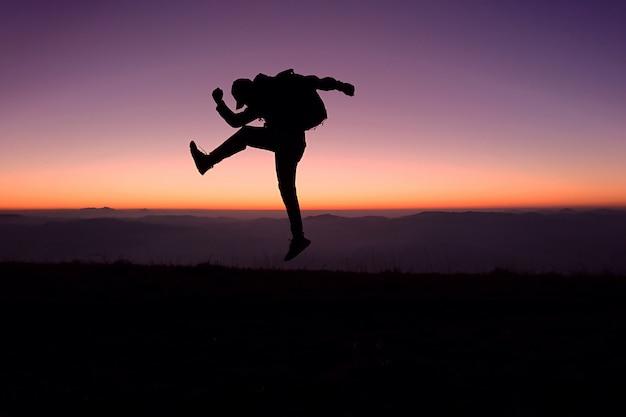 男旅行者のシルエットは、空の夕日に対して山を越えて崖から幸せにジャンプします。