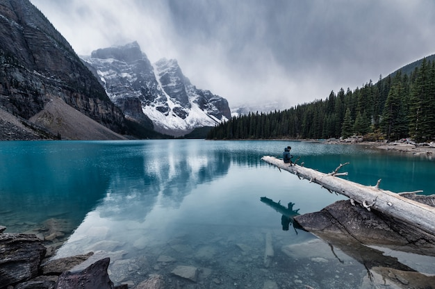 Man traveler sitting on timber in moraine lake on gloomy day at banff national park