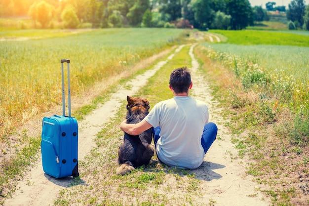 Путешественник человек сидит с собакой и дорожной сумкой на грунтовой дороге в поле летом обратно к камере. человек обнимает собаку и думает о своем путешествии