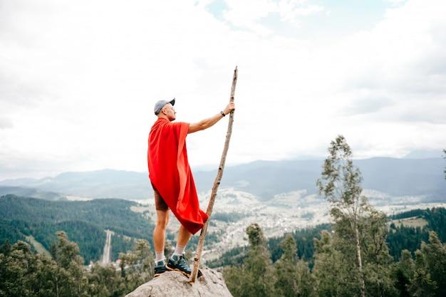 Человек путешественник, стоя на вершине горы с видом на природу пейзаж на фоне
