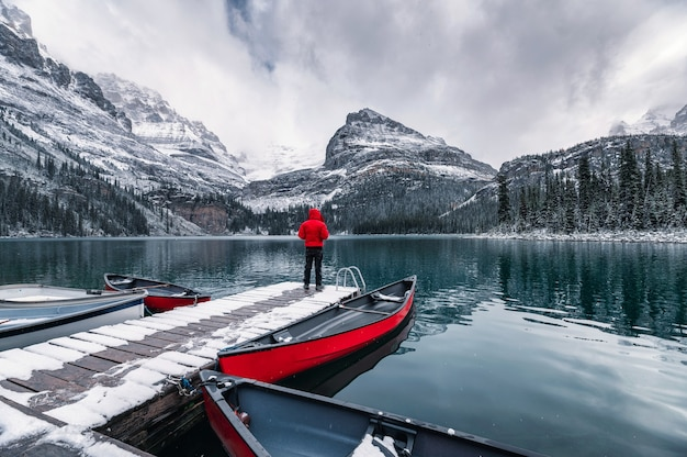 ヨーホー国立公園のオハラ湖のロッキー山脈のある木製の桟橋に立っている男性旅行者