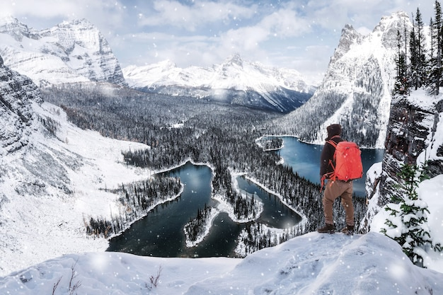 Man traveler standing on top of opabin plateau viewpoint in blizzard at yoho national park