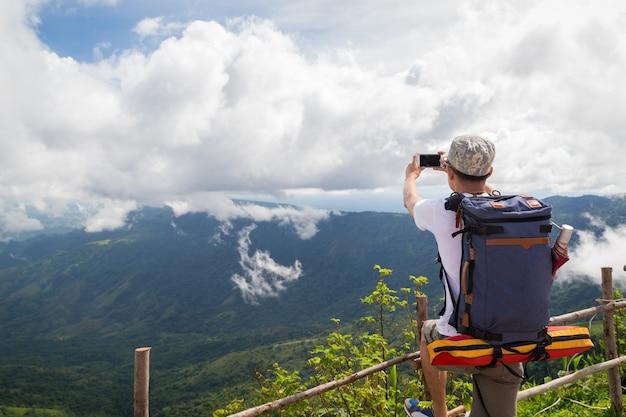 Man traveler take photo mountain view with mobile phone.