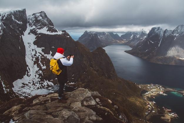 Man traveler taking photo with a smartphone hiking on reinebringen mountain ridge in norway lifestyle adventure traveling.