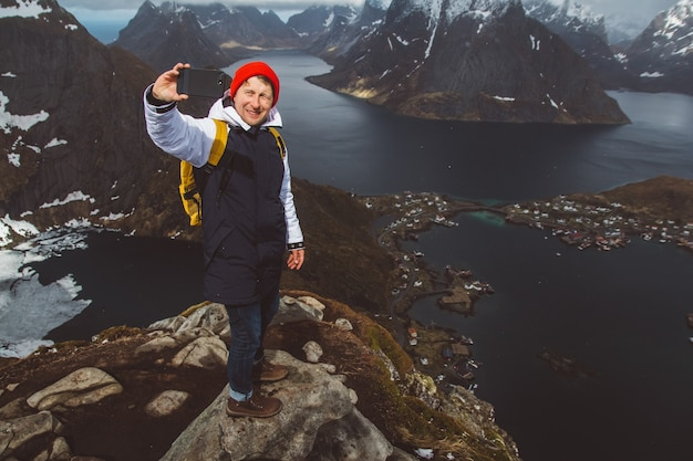 Man traveler taking self-portrait a photo with a smartphone hiking on reinebringen mountain ridge in norway lifestyle adventure traveling.