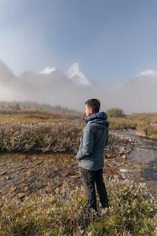 Путешественник в зимнем пальто стоит с горой ассинибойн в осеннем поле и ручей, текущим в провинциальном парке, канада