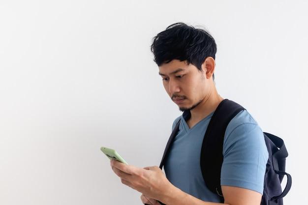 バックパックを持った男性旅行者が携帯電話アプリケーションを使用しています。
