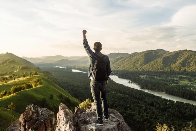 산 정상에 승자의 포즈에 제기 손으로 배낭 남자 여행자. 산에서의 여행과 휴가의 개념