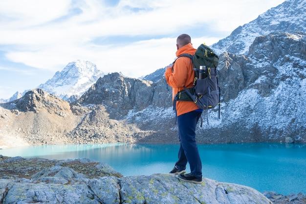 湖の上の崖の山で重いバックパックを持った男の旅行者旅行ライフスタイルアドベンチャー