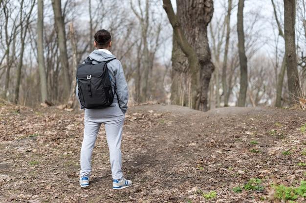 丘の頂上で休んで、春の森でバックパックハイキングを持つ男旅行者。旅行やスポーツのライフスタイルのコンセプト。極端な休暇の屋外。