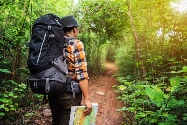 Man traveler with backpack and map in the forest