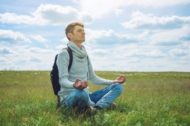 Man traveler with backpack sits on meadow with green grass under blue sky with clouds in the lotus position