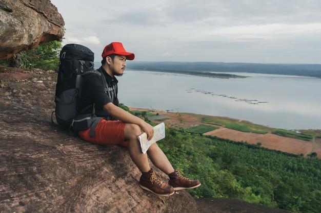 Человек путешественник с рюкзаком, сидя на краю обрыва, на вершине скалы горы