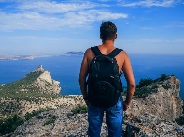 Man traveler with backpack standing on top of a mountain and looking out to the sea