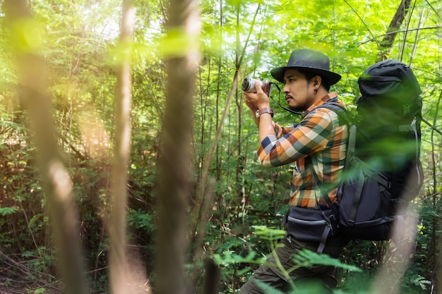 Man traveler with backpack using camera to take a photo in the forest