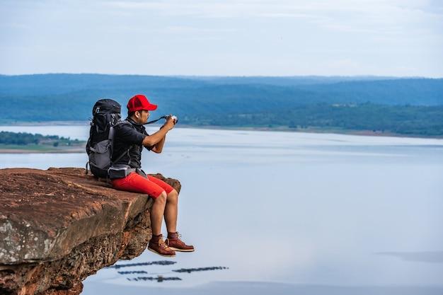 Человек путешественник с рюкзаком с помощью камеры, принимая фото на краю обрыва, на вершине скалы горы