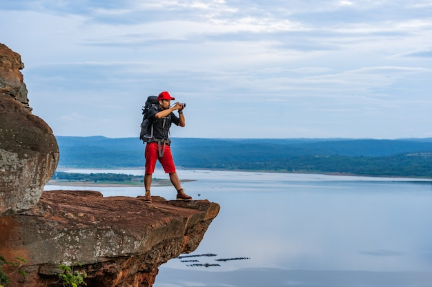 Man traveler with backpack using camera taking a photo on edge of cliff, on a top of the rock mountain