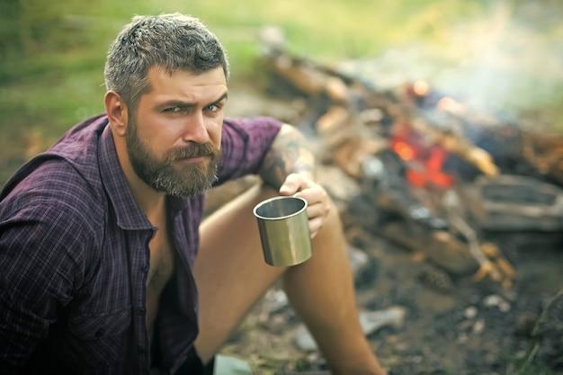 カップを持った男の旅行者は、自然の焚き火でリラックスします。