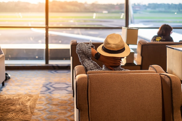 Man traveler with hat looking to airplane in the morning sunrise