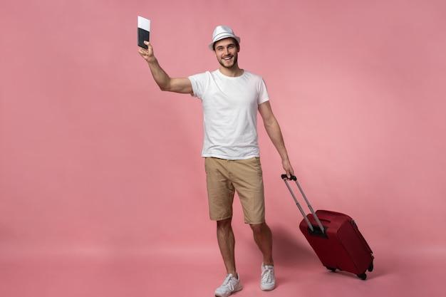 スーツケース、パスポート、チケットを持った男性旅行者。