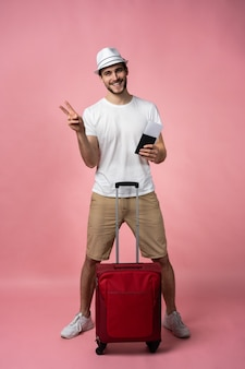 Man traveler with suitcase, passport and ticket.